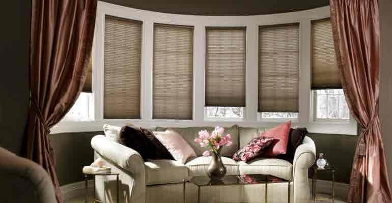 Brown honeycomb shades in living room bow window.
