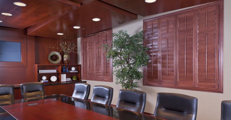 Brown-red shutters covering a window in a business conference room