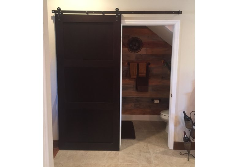 Dark brown barn door used as bathroom door 🚪