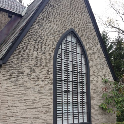 outdoor facade of stone home with plantation shutters