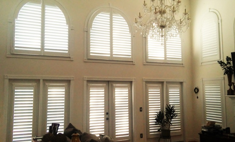 Great room in open concept Honolulu house with plantation shutters on arch windows.