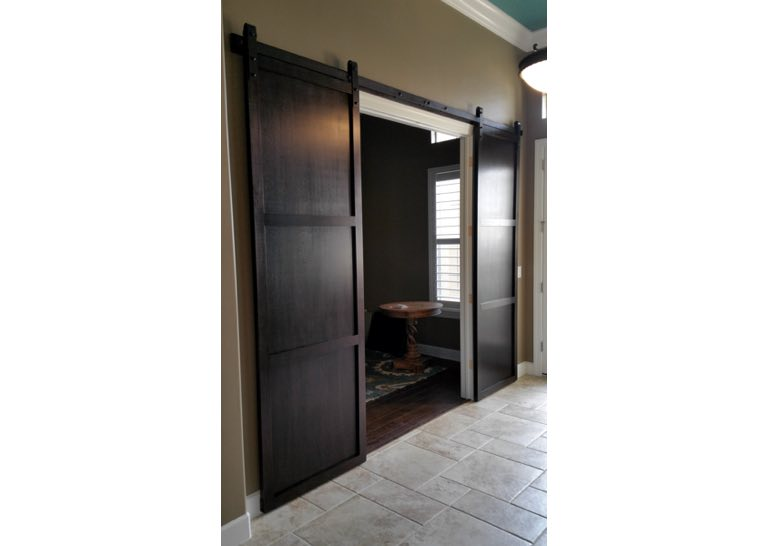 Dark brown sliding barn door covering home office entry 🚪