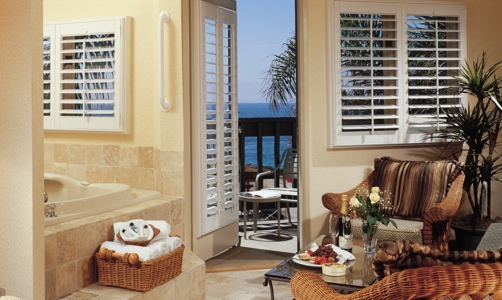 Plantation shutters on casement windows in a beachfront room.
