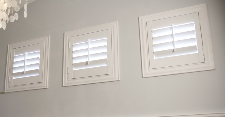 White shutters on three small square windows in laundry room