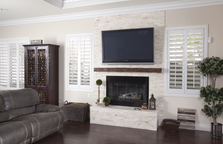 White plantation shutters in a Honolulu living room with solid hardwood floors.