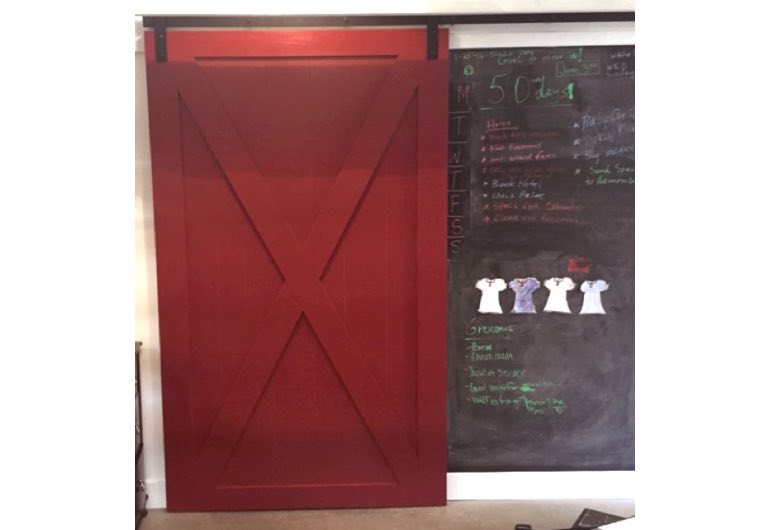 Red x-frame sliding barn door with black track next to chalkboard 🚪