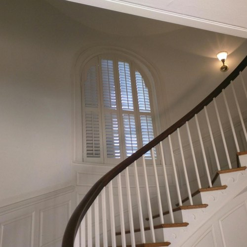 White plantation shutters covering arched window located in curved stairwell.