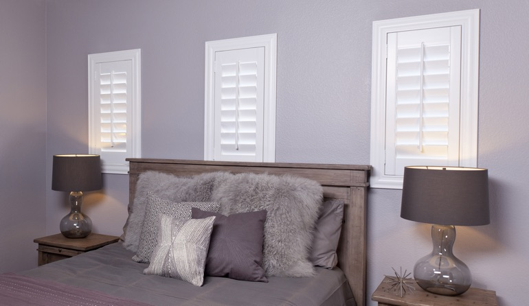 White plantation shutters in Honolulu bedroom windows.