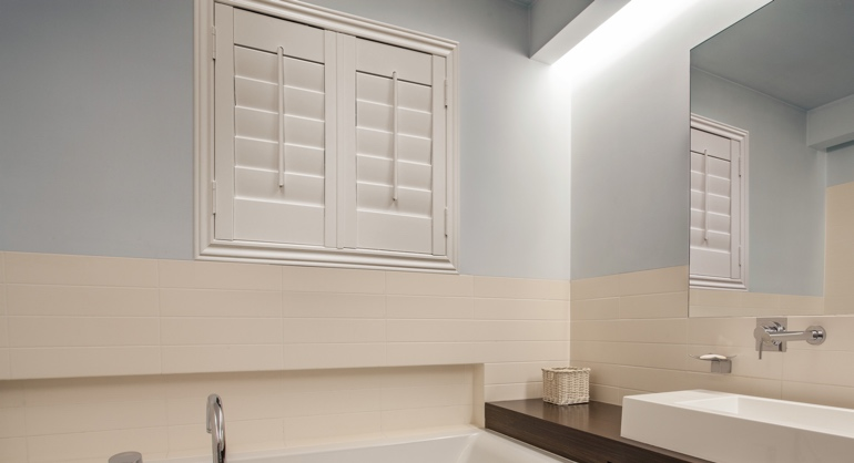 Plantation waterproof shutters in Honolulu bathroom.