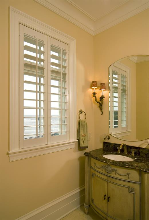White plantation shutters in a bathroom give a view of the ocean