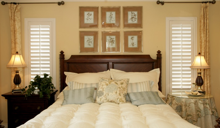 Beige bedroom with white plantation shutters covering windows in Honolulu