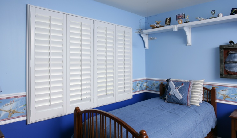 Blue kids bedroom with white plantation shutters in Honolulu