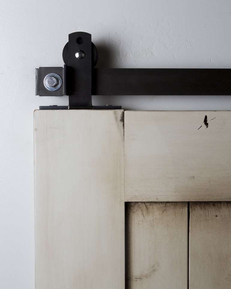 Black top-mounted mini ultra modern hanger on white rustic barn door